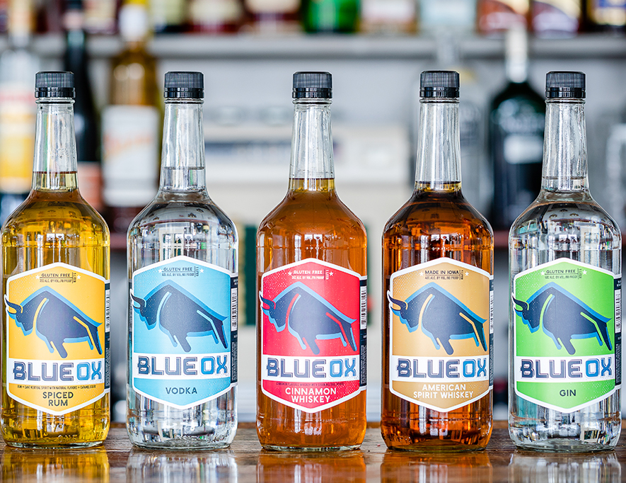 Six bottles of Blue Ox Spirits lined up on a counter