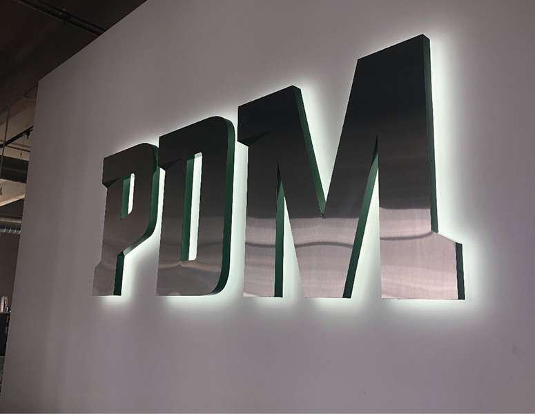 Metal PDM sign with backlighting on a white wall designed by Project7 Design
