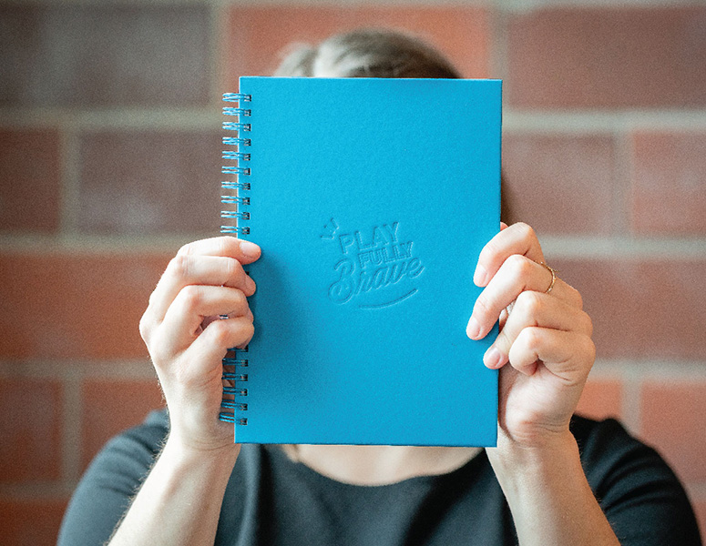 "Person holding blue notebook that says ""Play Fully Brave"""