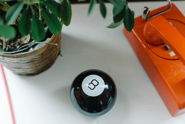 Magic 8 Ball on a white table next to a plant and orange telephone