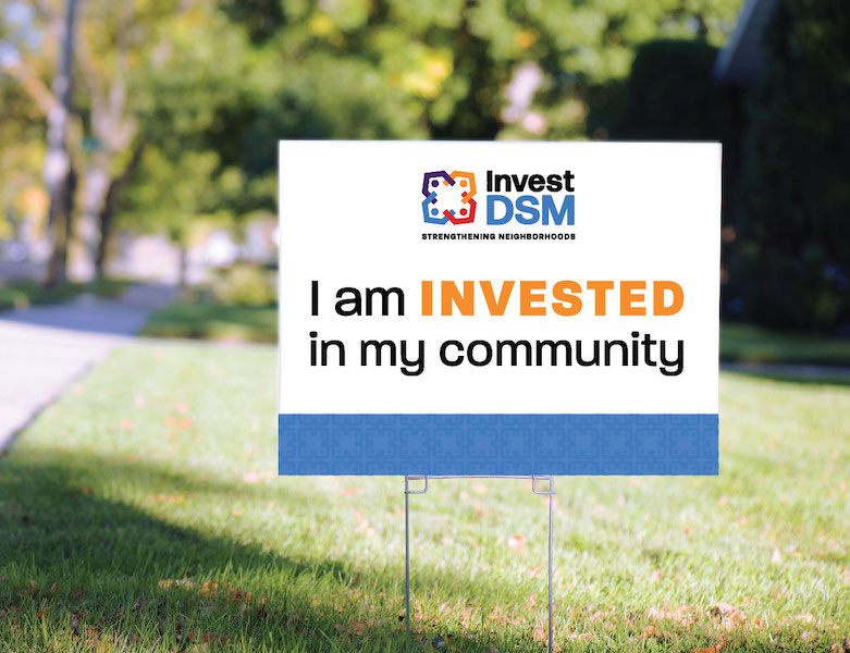 "Invest DSM yard sign that says ""I am invested in my community"""