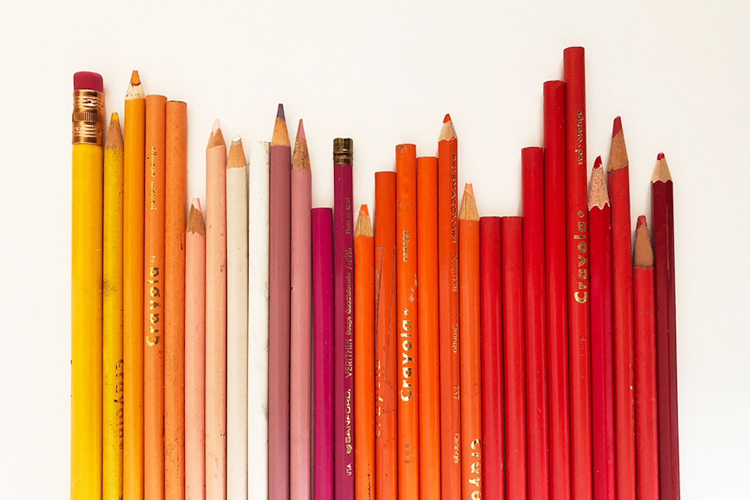 Image showing yellow, orange, pink and red colored pencils on a white table