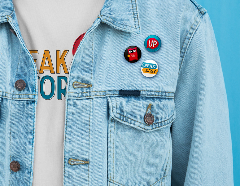 Speak Up Stories buttons on a denim jacket over a Speak Up Stories T-shirt