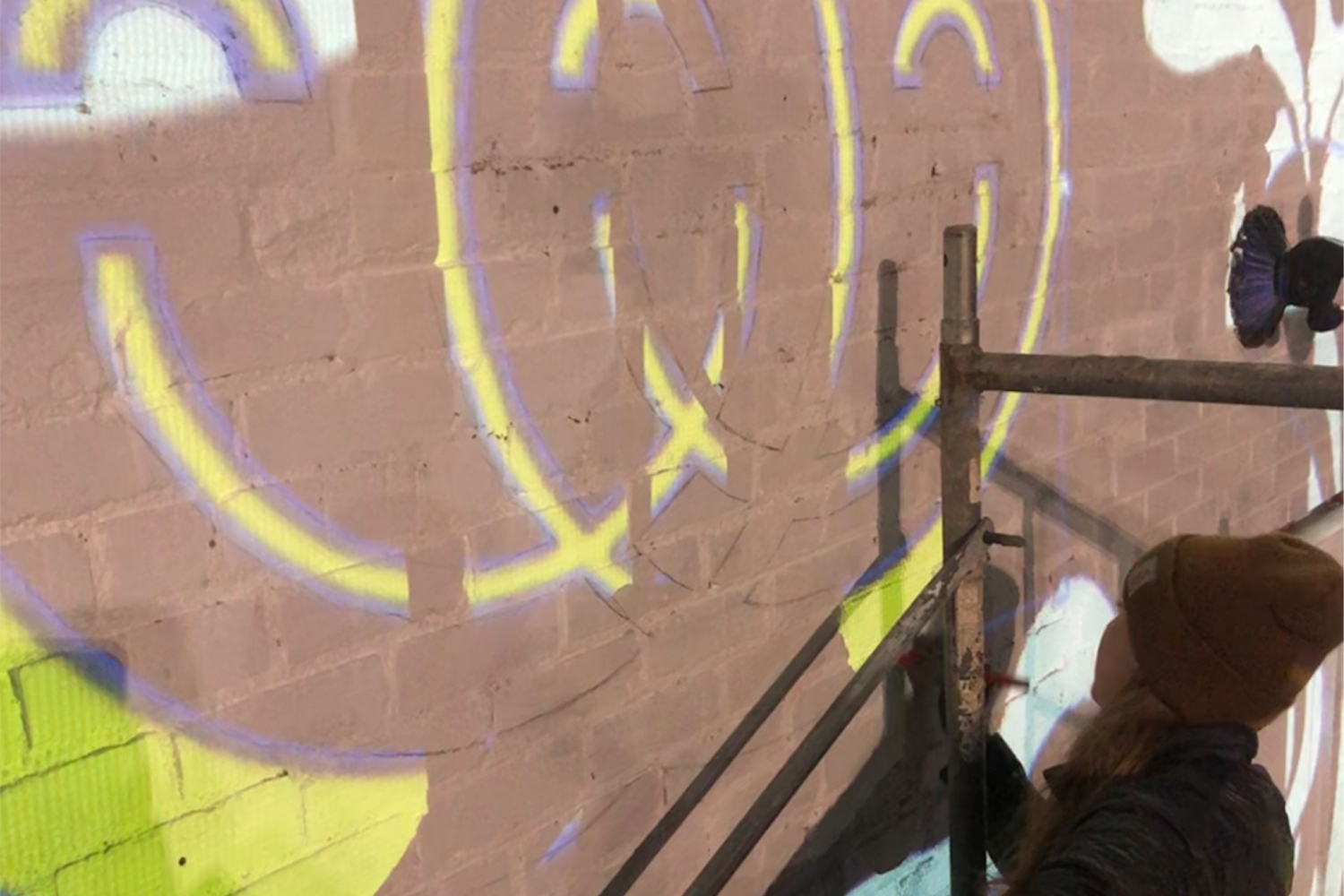 Person tracing mural on brick wall using projector