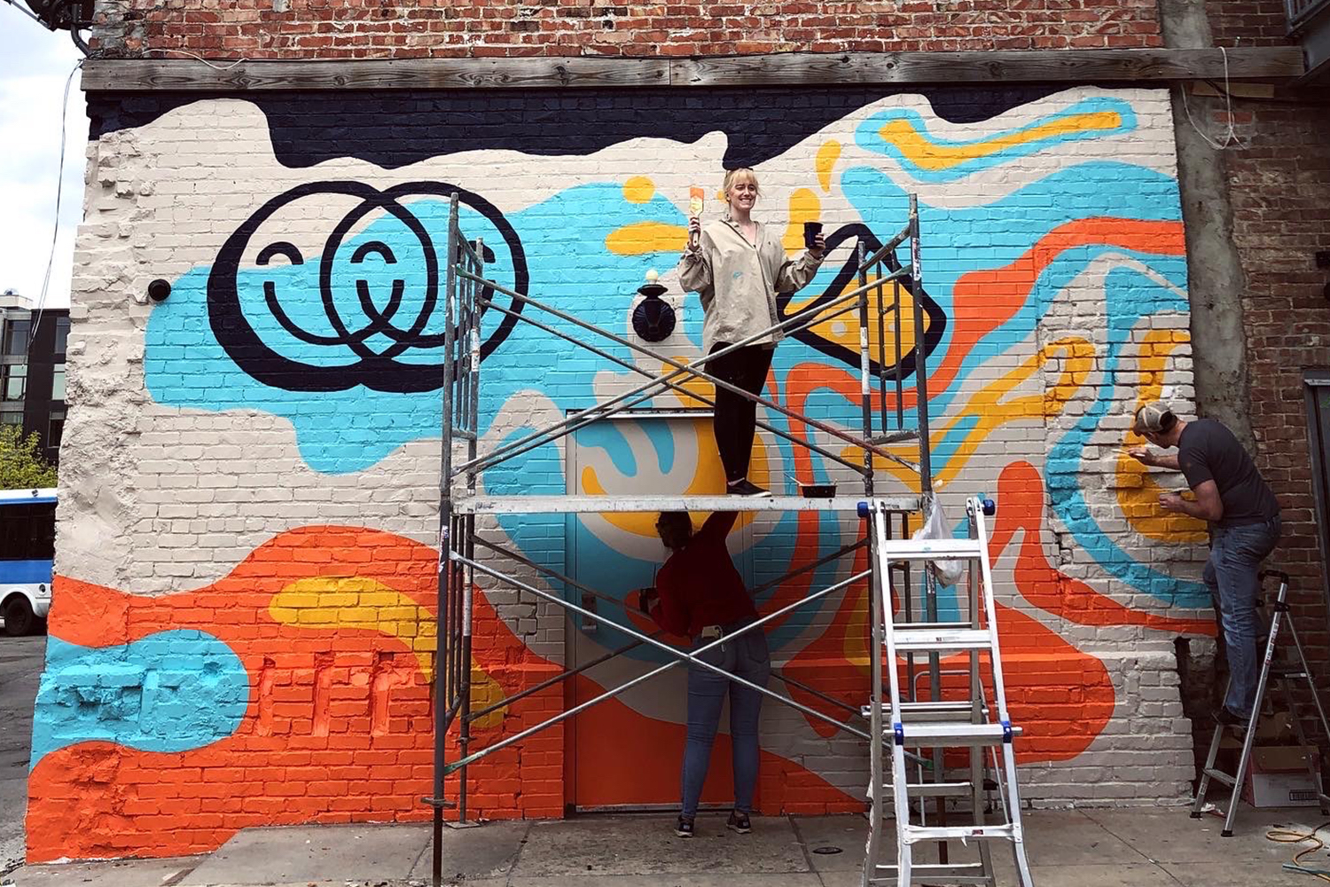 People standing on scaffolding painting a mural on a brick wall
